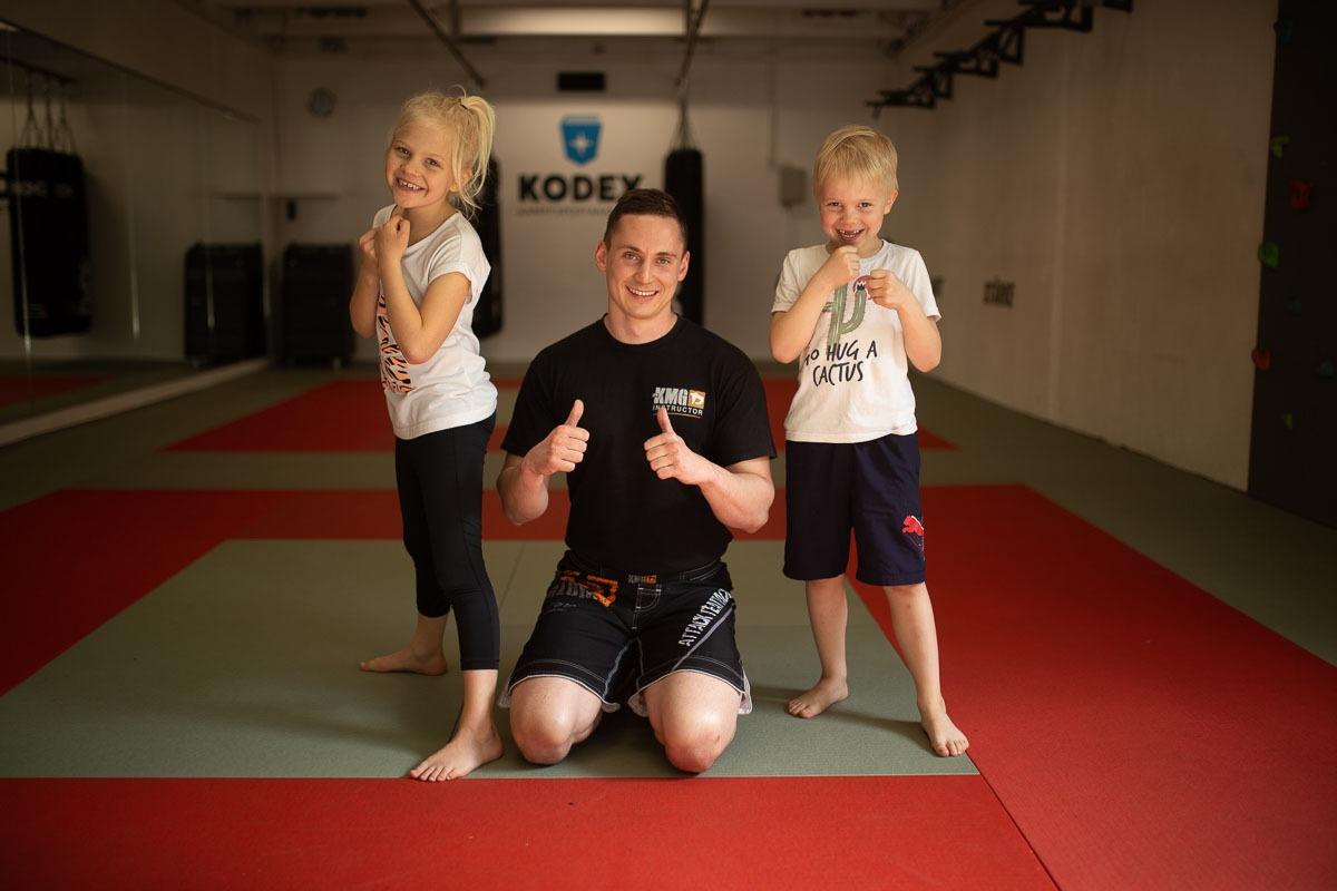 Victoria und Anton machen nach dem Selbstverteidigungskurs für Kinder ein Foto mit dem Krav Maga Global Trainer Kalle aus der Kodex Kampfsportakademie